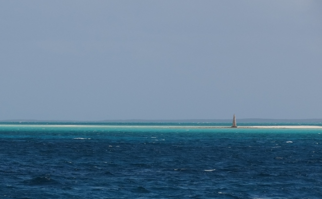 Very large sand bar marked with a stone beacon.