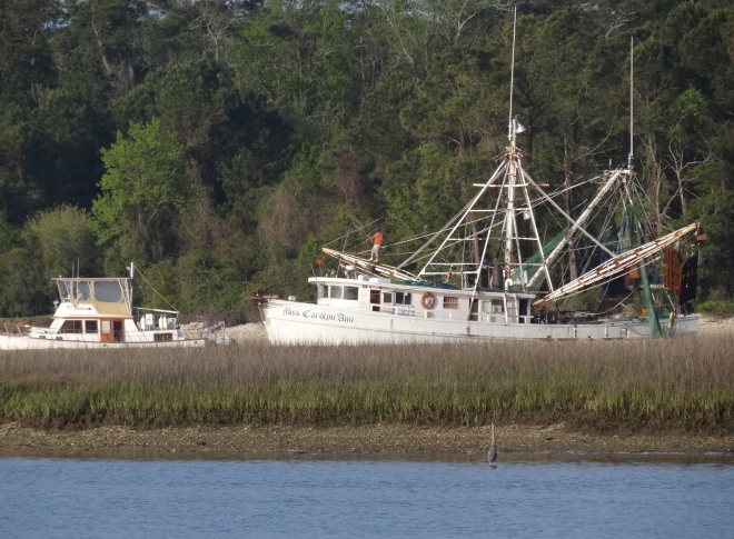 A trawler squeezes past a shrimper preparing to head out the inlet.