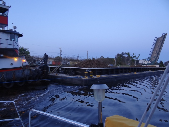A tug and barge pass by headed for the lock, the bridge still open behind them
