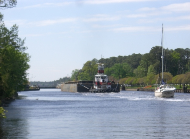 Tug and barge enter lock followed by sailboat
