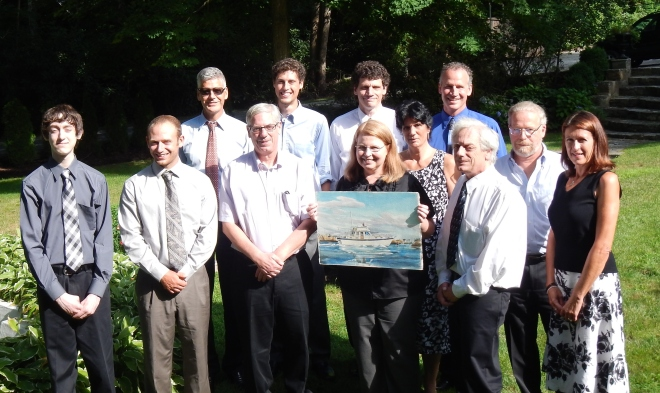 Group photo in the garden featuring a painting of m/v Spray