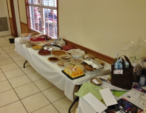 Dessert table with more to come, next to door prize table
