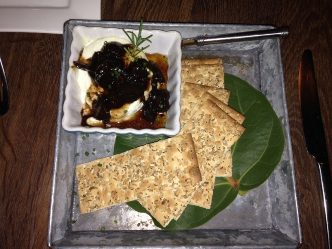 Lori's first course- warm goat cheese with honey-fig balsamic, mixed seeds flatbread crackers on SeaGrape leaves. Square plate of course