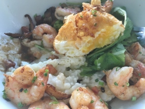 Gourmet shrimp and grits with bacon pieces and mushroom slivers. topped off by a deep fried egg!